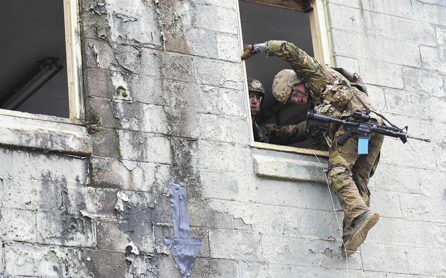 Best Ranger competitors climb out a window on Fort Benning, Ga.'s Urban Assault Course on the first day of 2021 competition consider among the Army's most grueling challenges.