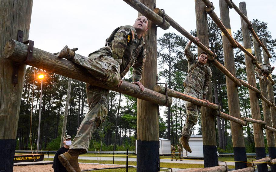 National Guard soldiers 1st Lt. Christian Briggs, left, and Spc. Jerry Marksbury navigate the Malvesti obstacle course, the second event in the Army's grueling three-day Best Ranger Competition on Friday, April 16, 2021 at Fort Benning, Ga.