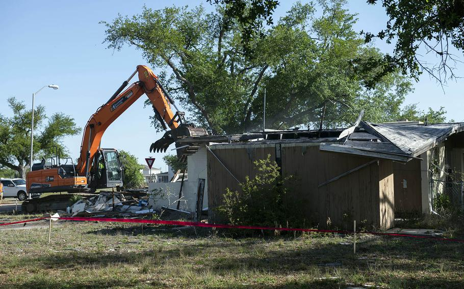 An excavator demolishes a house at Tyndall Air Force Base, Fla., April 1, 2021, that was severely damaged by Hurricane Michael in October 2018.
