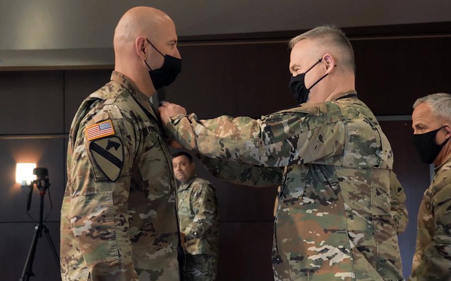 Brig. Gen. Gregory Day, land component commander, pins the Soldier's Medal on Sgt. 1st Class Jedidia Powell at Camp Withycombe, Ore., April 10, 2021. Powell repeatedly ran into a burning house and helped two women and a dog to safety in November 2017.