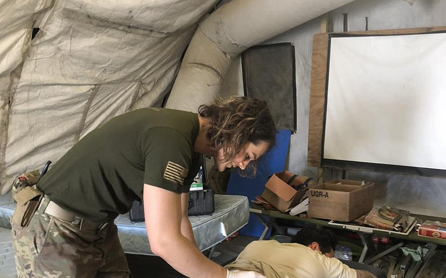 Then-Capt. Alivia Stehlik, a transgender service member, provides physical therapy for a soldier while deployed to Afghanistan in 2018.