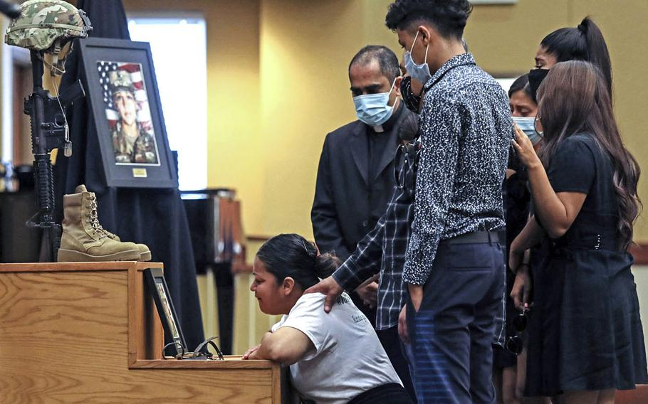 The family of Spc. Vanessa Guillen grieves in front of her Soldier's Cross during her unit memorial ceremony at Fort Hood, Texas, on July 17. Several hundred people — family, friends and fellow soldiers — attended the ceremony in the post's Spirit of Fort Hood Chapel.