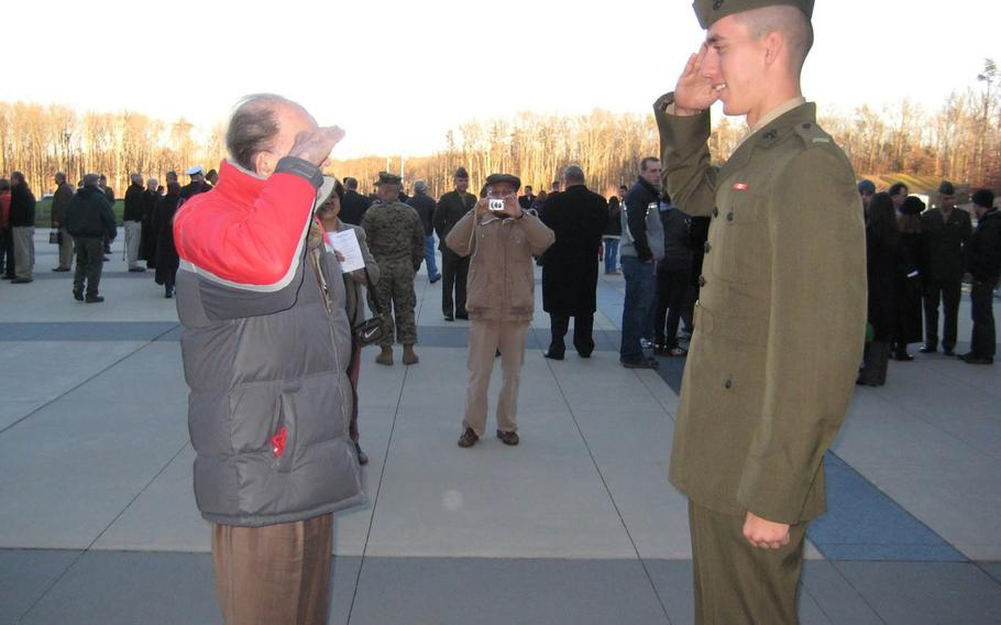 U.S. Marine Corps veteran Jack Zovack, left, salutes his nephew, then-2nd Lt. Patrick Weeks, for the first time at Weeks' commissioning ceremony in Quantico, Va., Dec. 11, 2009. Zovack, who served in WWII and Korea, wore civilian clothes for the ceremony.