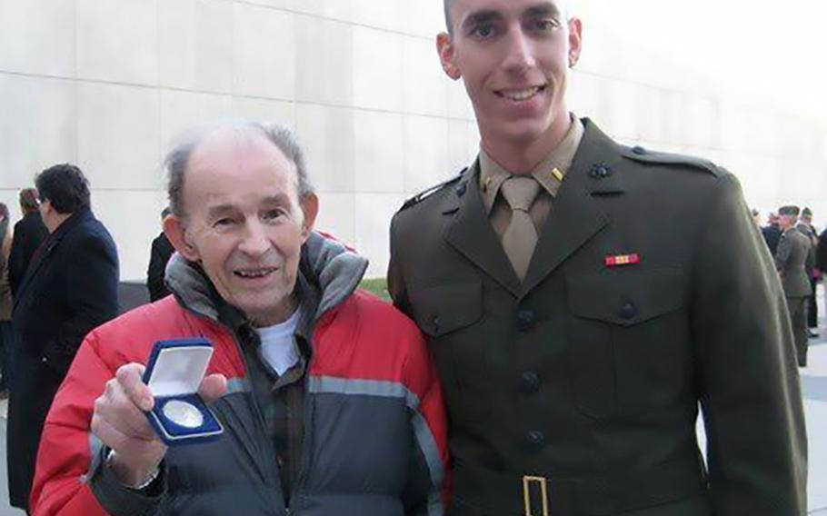 Jack Zovack, left, holds up the silver coin he was given by his nephew, then 2nd Lt. Patrick Weeks, right, at Weeks' commissioning as a U.S. Marine Corps officer at Quantico, Va., Dec. 11, 2009. Zovack, who served in the Pacific in WWII and in the Korean war, gave Weeks his first salute.