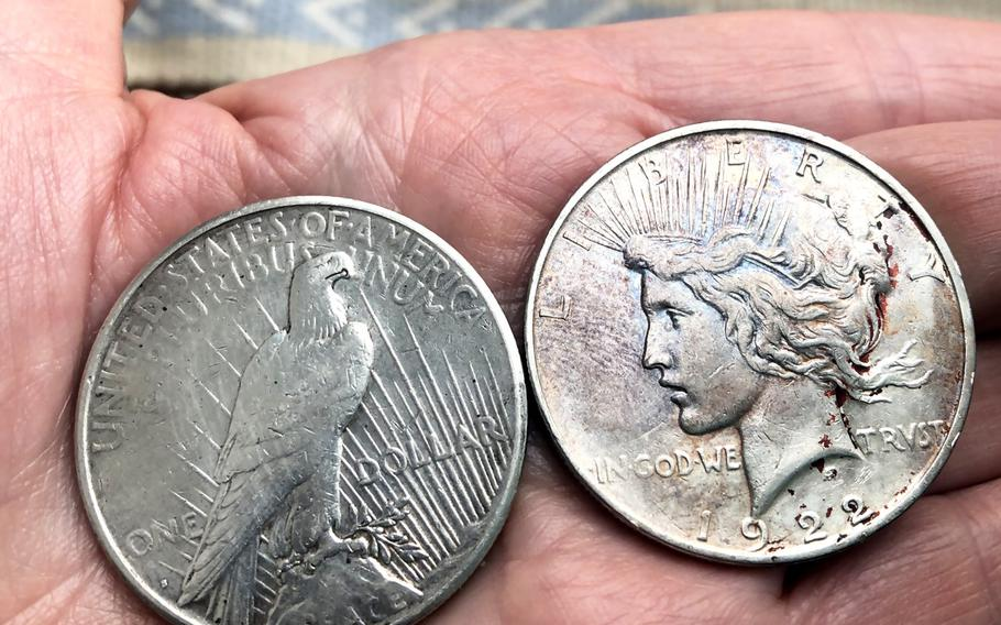 The back and front of two silver dollar peace coins from 1922 and 1923. Peace coins are popular as the silver coin that newly commissioned officers give to the person who  salutes them for the first time.