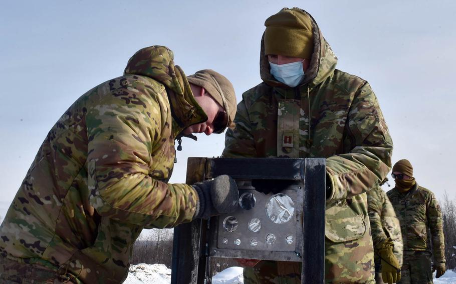 Airmen attach the metal plates of a bikini gauge used in testing snow barriers to mitigate shockwaves from detonations at Eielson Air Force Base, Alaska, March 18, 2021.