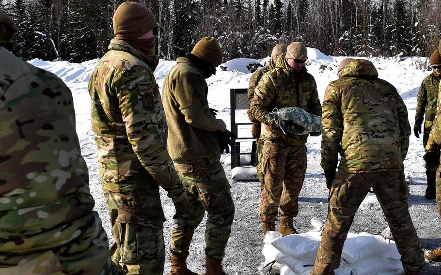 Airmen place snow-filled bags around an explosive charge during an experiment at Eielson Air Force Base, Alaska, March 18, 2021.