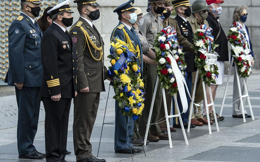 Veterans and other wreath-layers pose during a ceremony at the National World War II Memorial in Washington, D.C. on May 8, 2021, the anniversary of the end of the war in Europe.