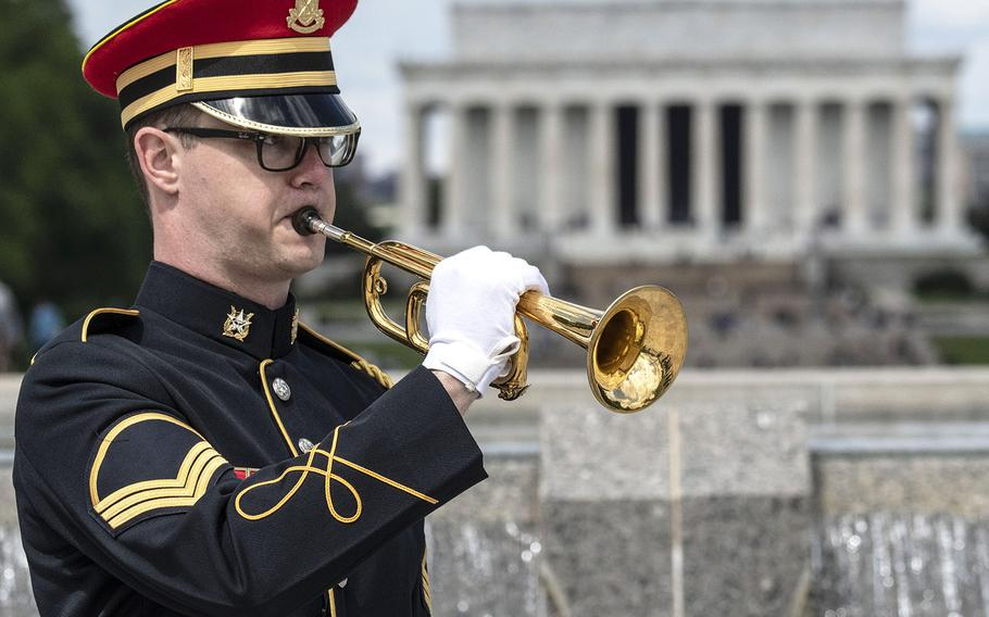 Staff Sgt. Andrew Boylan of Houston, Texas, a member of the U.S. Army Band, plays taps during a ceremony at the National World War II Memorial in Washington, D.C. on May 8, 2021, the anniversary of the end of the war in Europe.