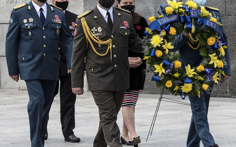 A Ukrainian delegation including Defense Attache Maj. Gen. Borys Krementskyi, left, and Ambassador Extraordinary and Plenipotentiary to the U.S. Markarova Oksana, center background, prepares to lay a wreath during a ceremony at the National World War II Memorial in Washington, D.C. on May 8, 2021, the anniversary of the end of the war in Europe.