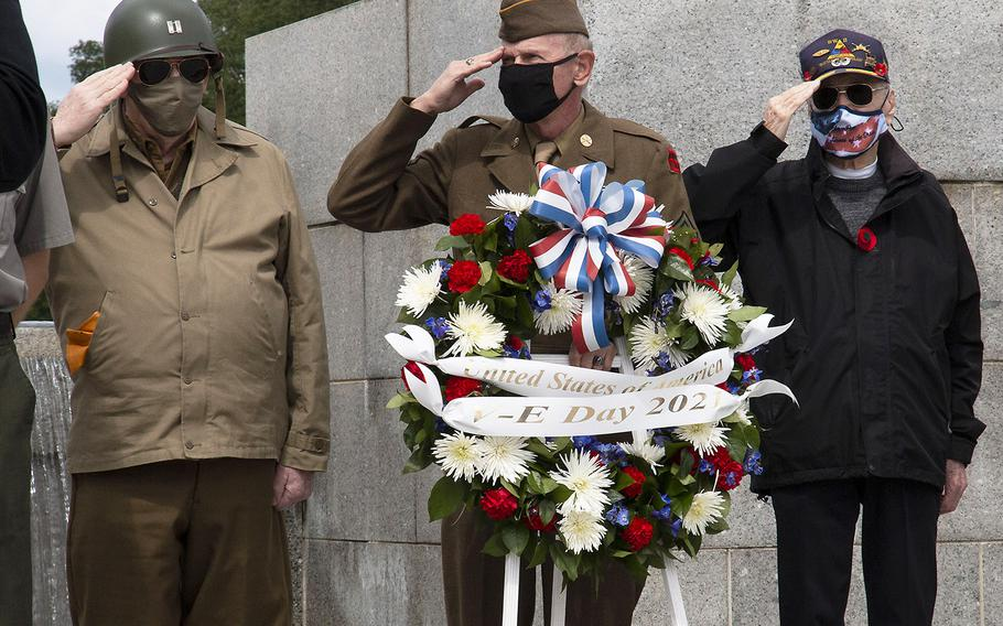 National Park Service volunteer and reenactor Patrick McCourt, Vietnam-era veteran Sidney O. Wade Jr. and World War II veteran Harry Martin, left to right, salute as the national anthem is played during a ceremony at the National World War II Memorial in Washington, D.C. on May 8, 2021, the anniversary of the end of the war in Europe.