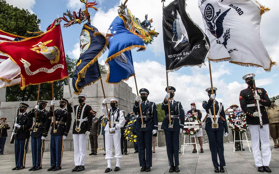 The Military District of Washington Armed Forces Color Guard battles the wind as the national anthem is played during a ceremony at the National World War II Memorial in Washington, D.C. on May 8, 2021, the anniversary of the end of the war in Europe.