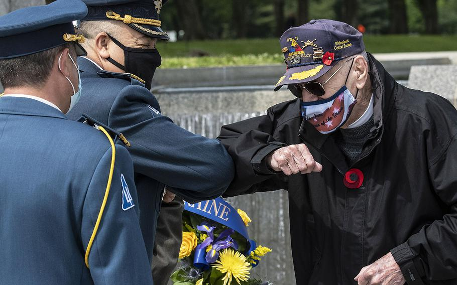 World War II veteran Harry Miller elbow-bumps Ukrainian Defense Attache Maj. Gen. Borys Krementskyi before a ceremony at the National World War II Memorial in Washington, D.C. on May 8, 2021, the 76th anniversary of the end of the war in Europe. Last year's planned 75th anniversary ceremonies were canceled due to the pandemic.