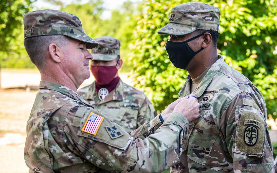 Maj. Gen. Patrick J. Donahoe, Maneuver Center of Excellence commanding general, presents the Soldier's Medal to Capt. Christopher D. Long at Fort Benning, Ga., May 7, 2021. Long tried to save the life of a soldier who was stabbed by her husband by pulling him off the victim and calling for emergency aid.