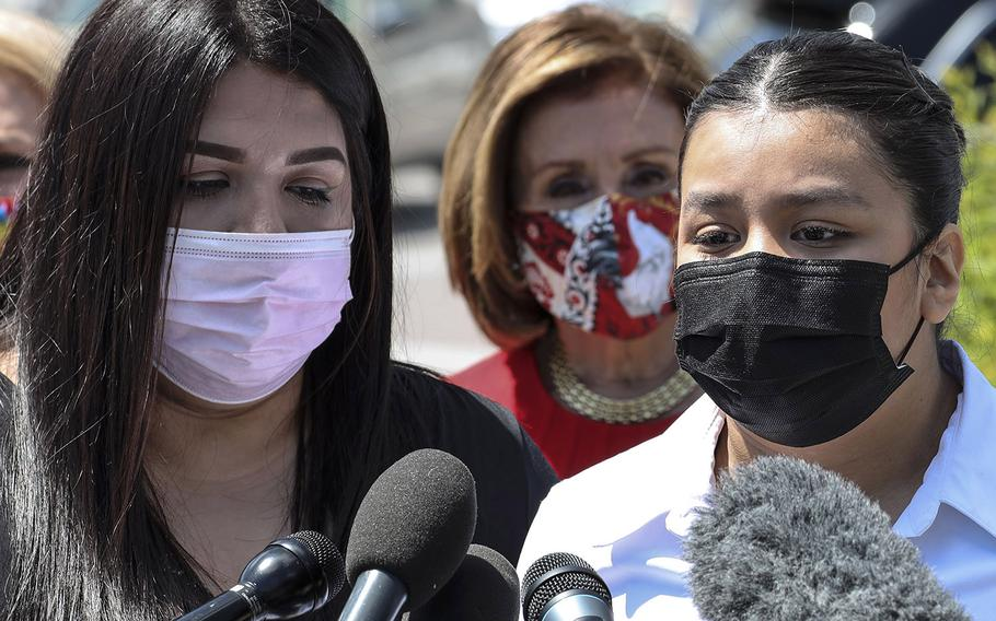 """Mayra, left,  and Lupe Guillen, sisters of slain U.S. Army Pfc. Vanessa Guillen, speak at a Capitol Hill news conference to reintroduce the """"I am Vanessa Guillen Act"""" on May 13, 2021. Behind them is House Speaker Nancy Pelosi."""