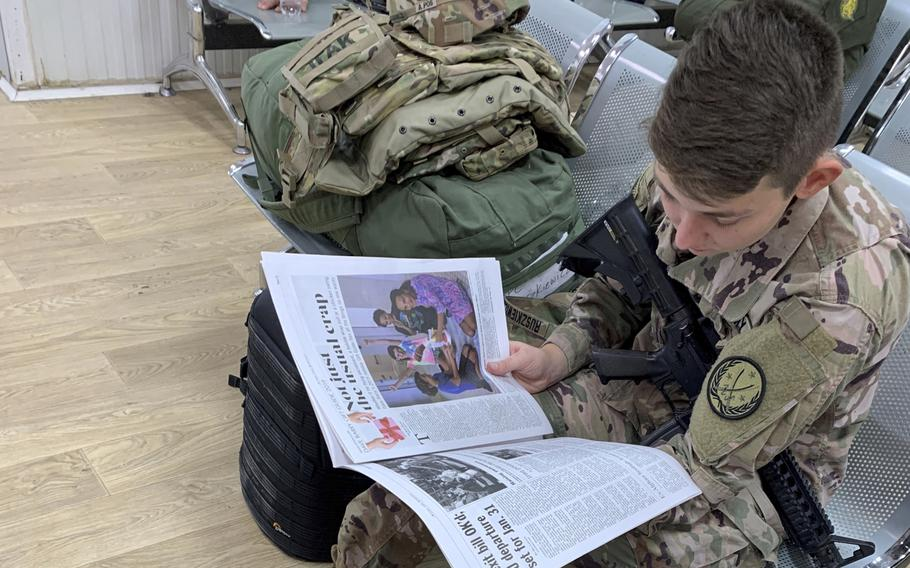 Spc. Angel Ruszkiewicz, 21, a combat camera specialist from Milwaukee, Wi., reads a Stars and Stripes at the passenger terminal on a coalition base in Erbil, Iraq, on Monday, Dec. 23, 2019, before a flight to Syria.