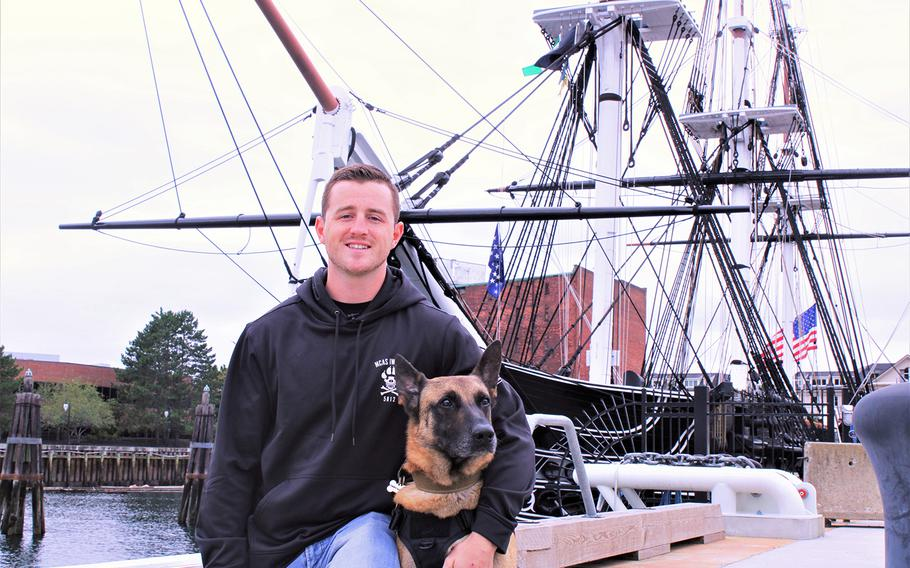 US Marine veteran Brendan Cabey poses with his newly adopted - and newly retired military working dog - Ramos in front of the USS Constitution on Sept. 11, 2020.