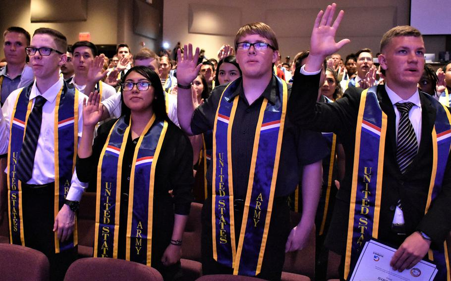 Army recruits raise their right hands while reciting the oath of enlistment during a 2019 induction ceremony at Calvary Community Church in Glendale, Ariz., on Friday, April 26, 2019.