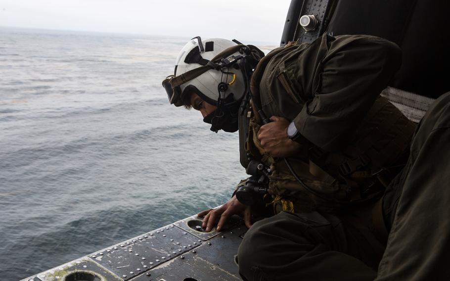 Petty Officer 2nd Class Joseph Rivera, a search and rescue swimmer assigned to the amphibious assault ship USS Makin Island, looks out of a U.S. Navy MH-60 Seahawk while conducting search and rescue relief operations following an AAV-P7/A1 assault amphibious vehicle accident off the coast of Southern California, July 30, 2020.
