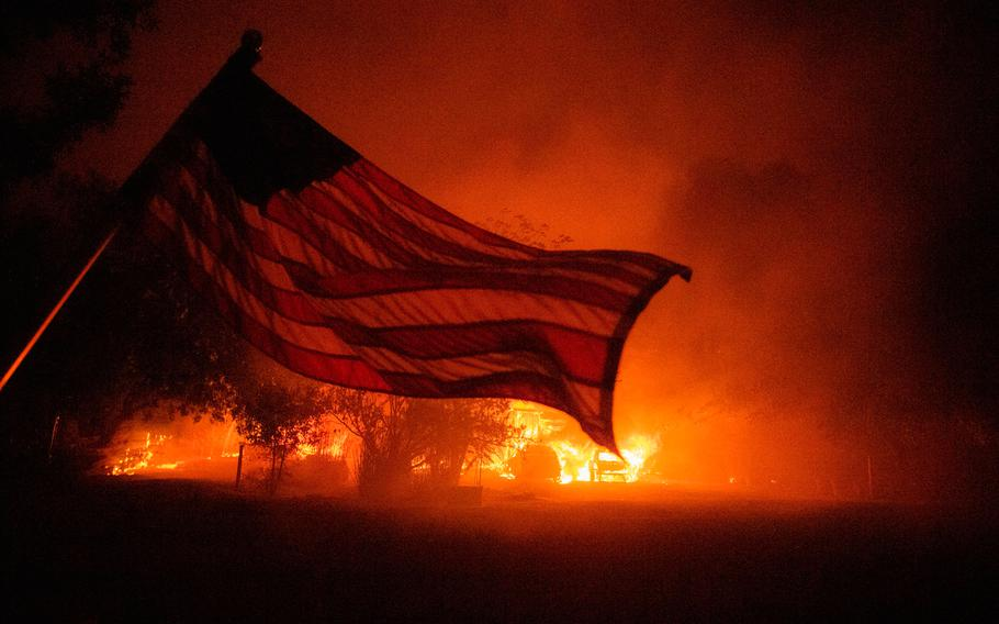 An American flag blows in the wind in front of a burning home in Vacaville, California during the LNU Lightning Complex fire on August 19, 2020.