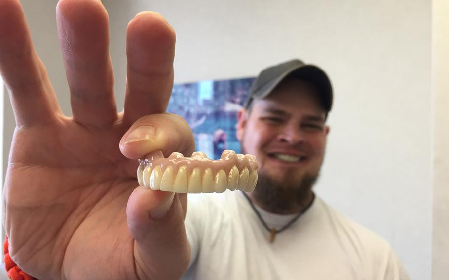 Dustin Kirby holds a new set of customized teeth, fashioned for him by a medical staff from Northwell Health. Kirby, a former Navy corpsman grievously wounded by a sniper's bullet in 2006, is scheduled to share his story of recovery at Side by Side, a Northwell-sponsored music event at  New York's Fleet Week 2019.