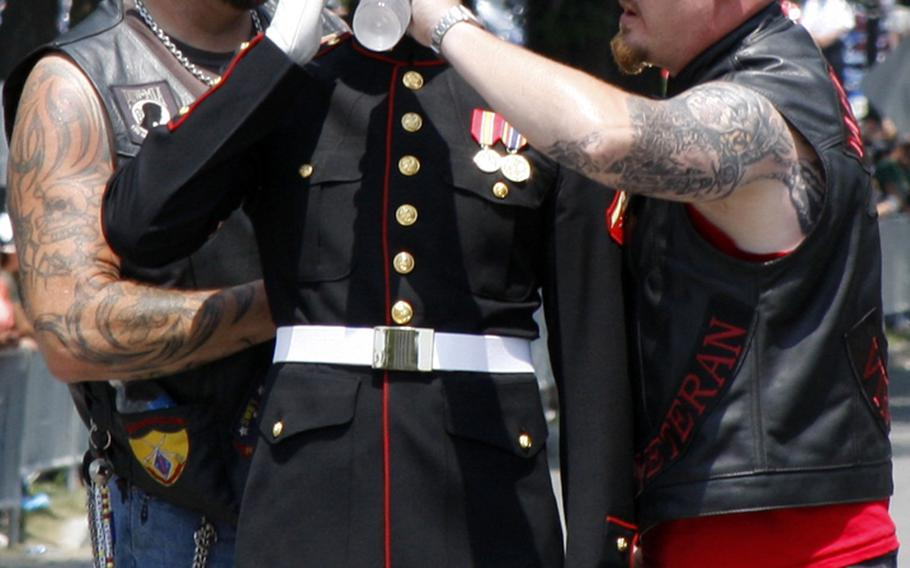 As a Marine salutes the Rolling Thunder riders in 2013, he gets some relief from the heat from a couple of participants.