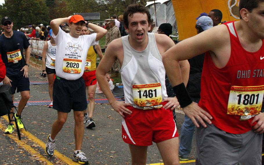 Finishers catch their breath after crossing the finish line at the Marine Corps Marathon on Oct. 28, 2012.