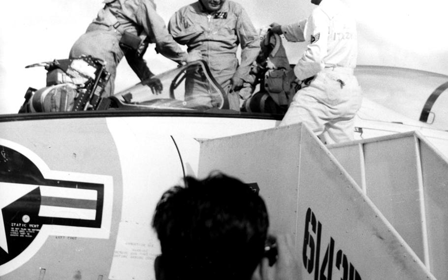 Rep. Daniel Inouye (D-Hawaii) emerges from the cockpit of an F9F8T jet trainer at Itazuke Air Base, Japan, in 1960. Inouye and the plane's pilot, Maj. Robert H. Klingman, left, flew in from Tokyo so the congressman could visit his ancestral home at nearby Yokoyama.