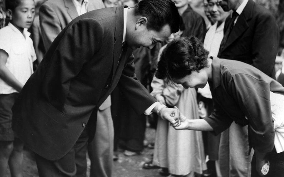 Rep. Daniel K. Inouye (D-Hawaii) is welcomed to his ancestral village of Yokoyama, Japan, by a relative in 1960.