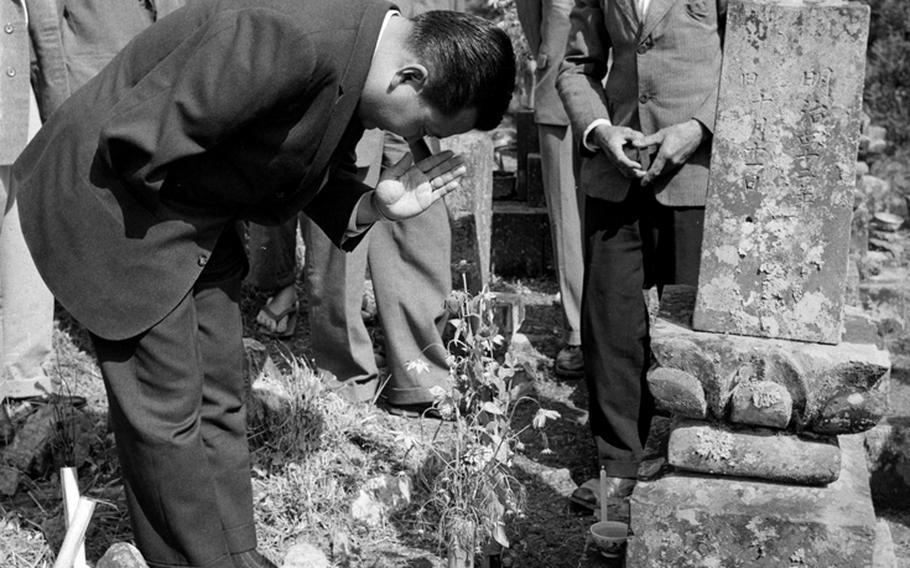 Rep. Daniel K. Inouye (D-Hawaii) offers a prayer the grave of his great-grandfather at Yokoyama, Japan, in 1960.