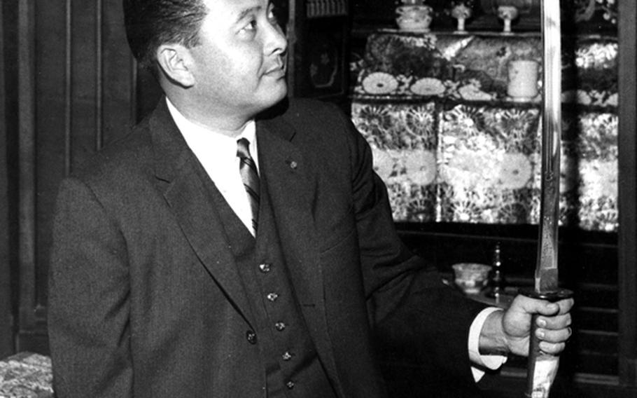 Rep. Daniel K. Inouye (D-Hawaii) admires a sword presented to him by residents of Yokoyama, Japan, during a 1960 visit to his ancestral home village.