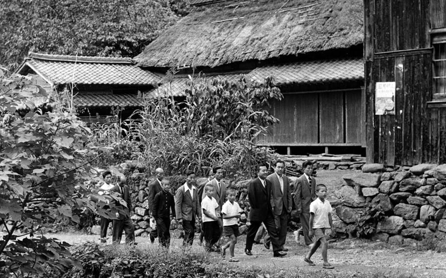 Rep. Daniel K. Inouye (D-Hawaii), in dark suit, strolls through the mountain village of Yokoyama, Japan, his ancestral home, in 1960.