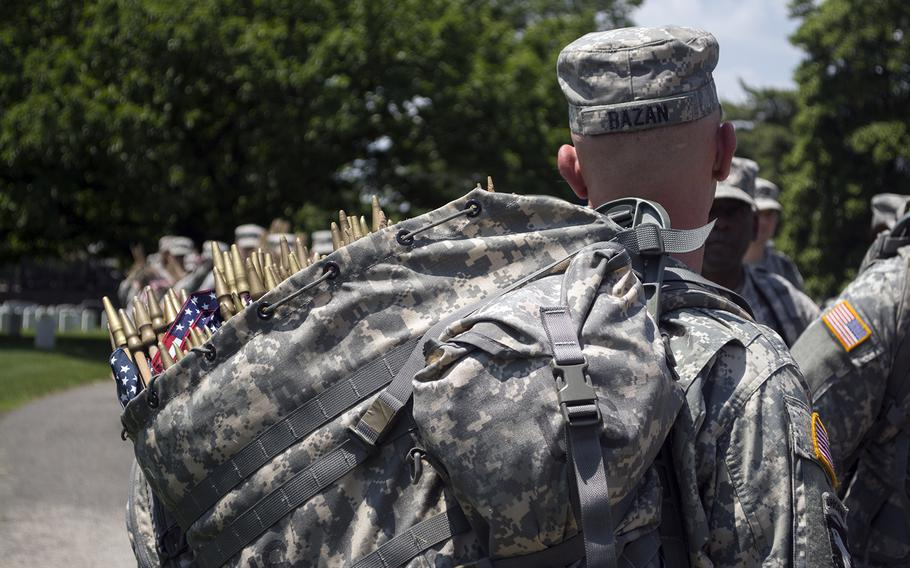 """A soldier carries a bag containing some of the more than 200,000 flags that were planted during the """"Flags In"""" event at Arlington National Cemetery on May 22, 2014."""