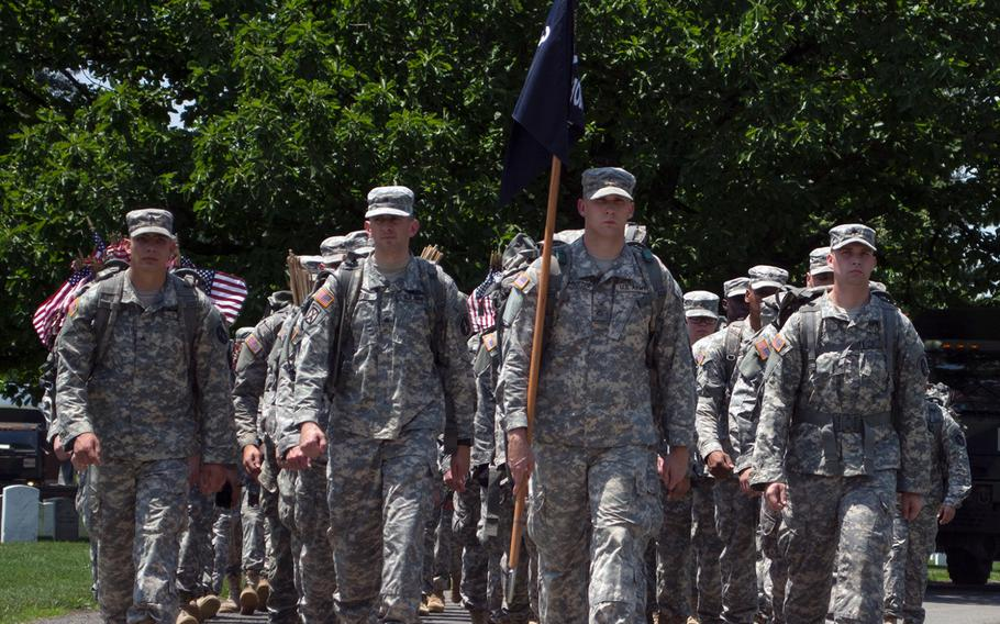 """Soldiers from the Old Guard march through Arlington National Cemetery as part of the """"Flags In"""" event."""