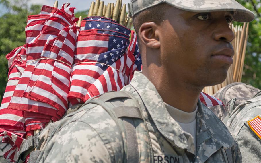 A soldier from the Old Guard carries flags on his back as he and others fanned out across Arlington National Cemetery. About 1,000 soldiers took part.