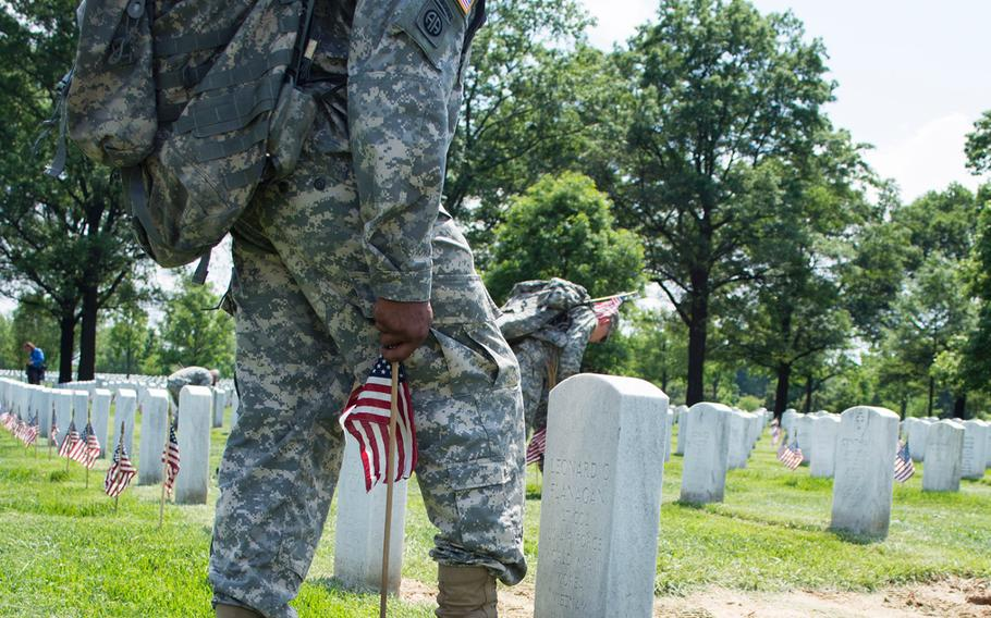 The ritual: Toe of the combat boot placed against the center of a headstone, flag planted at the heel.