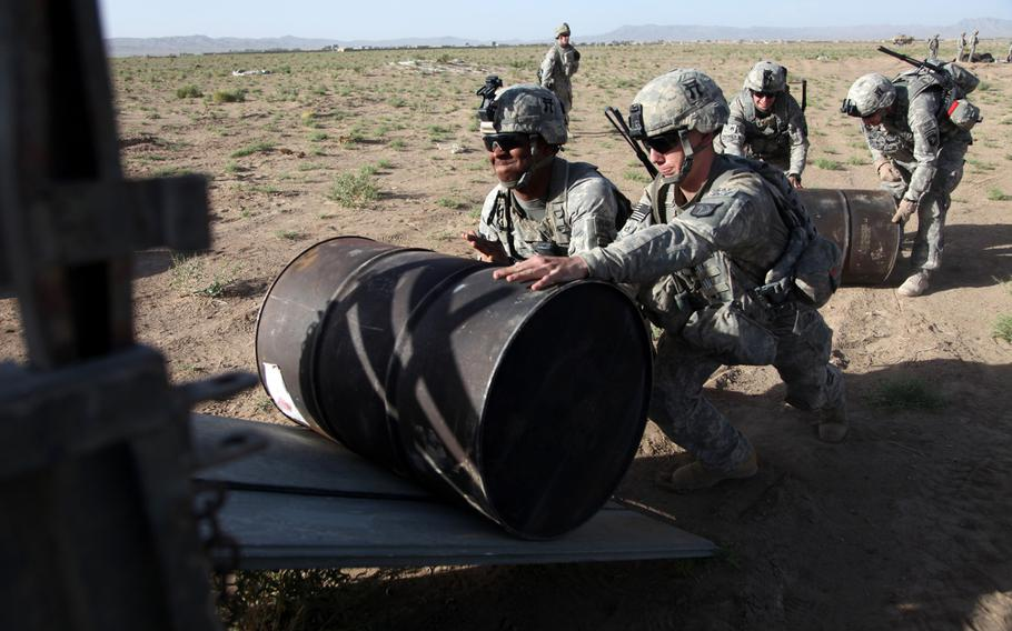U.S. soldiers roll barrels of fuel onto a truck during a fuel drop at Forward Operating Base Waza Kwah, Paktika Province, Afghanistan, in July 2010. According to a new documentary film, ''The Burden,'' the annual cost for the U.S. to guard the world?s shipping ''chokeholds'' - Turkish Straits, Suez Canal, Strait of Hormuz and Strait of Malacca - is $85 billion.
