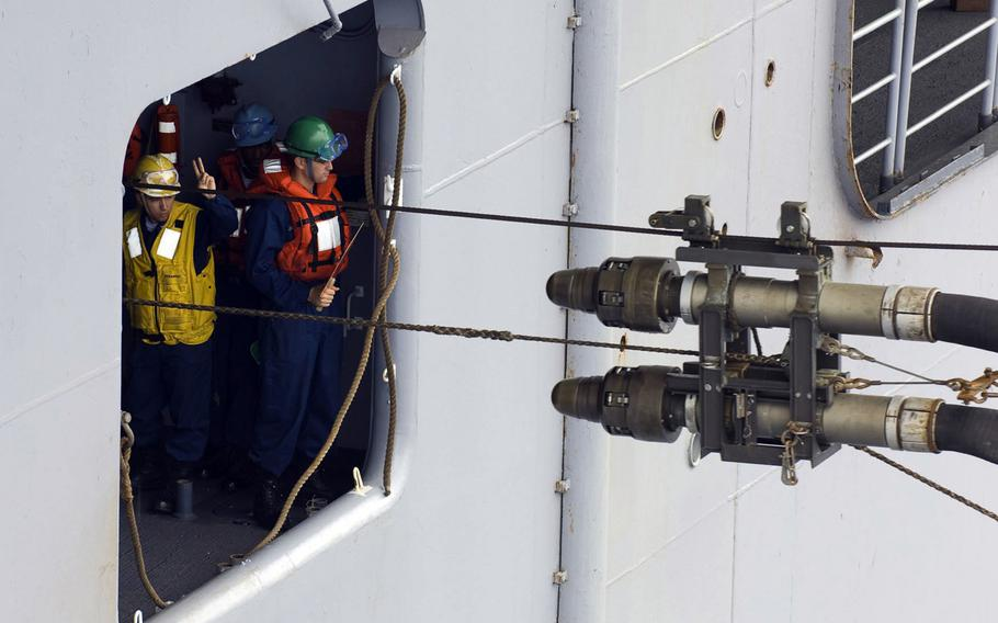 """Sailors aboard the amphibious assault ship USS Essex receive fuel lines from the Military Sealift Command fleet replenishment oiler USNS John Ericsson during a refueling at sea in June 2009. ''Fossil fuel to keep a large force going is really a tremendous burden,"""" according to former Marine Gen. Anthony Zinni."""