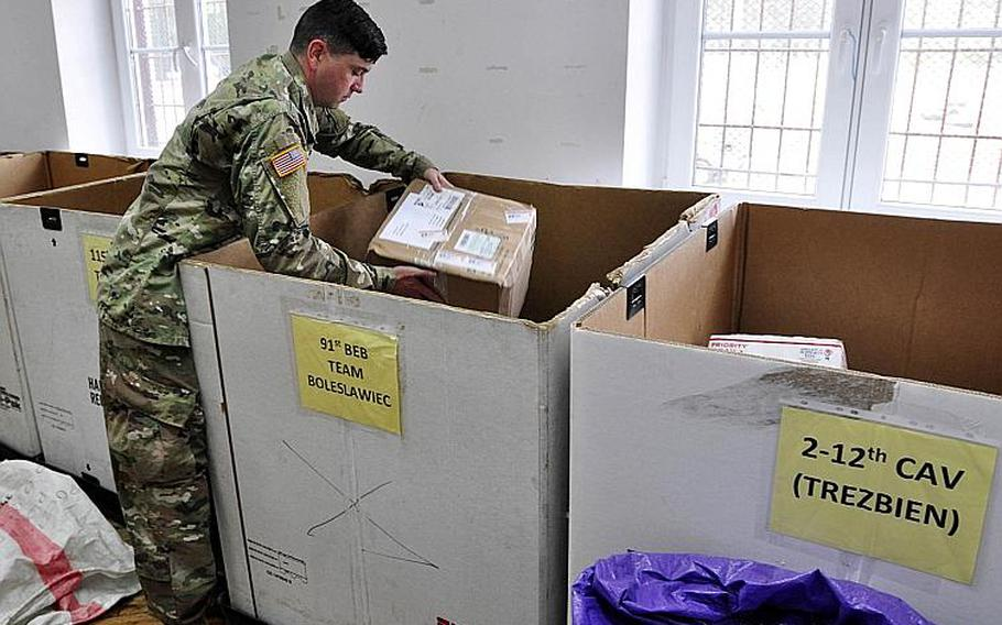 Postal clerk Spc. Thomas Gallen places a package into a receiving company's outbox in Zagan, Poland, June 26, 2018.