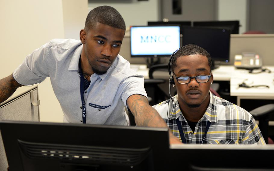 A supervisor helps a customer service agent with a call at the MyNavy Career Center at Navy Personnel Command in Millington, Tenn.