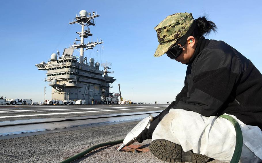 A sailor performs maintenance on the flight deck of the aircraft carrier USS Harry S. Truman at Norfolk, Va., March 13, 2019.
