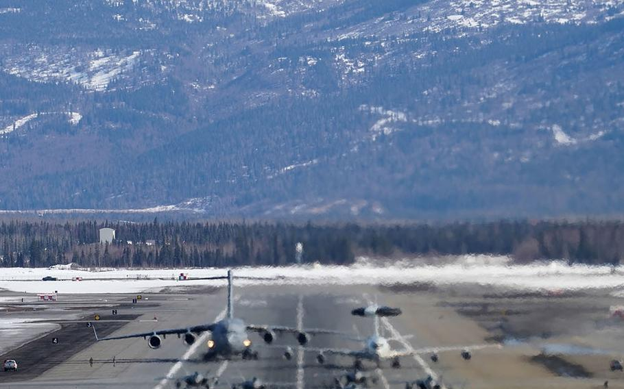F-22 Raptors participate in an elephant walk with an E-3 Sentry and a C-17 Globemaster III at Joint Base Elmendorf-Richardson, Alaska, Wednesday, March 26, 2019.