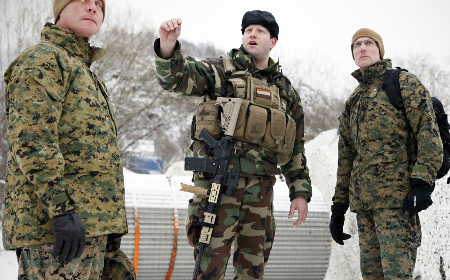Col. Mark A. Smith, deputy commander, 24th Marine Regiment, 4th Marine Division, left, and Brig. Gen. James M. Lariviere, commander of 4th Marine Division, talk to a Dutch soldier while awaiting a landing craft which would take them aboard a Dutch ship in 2012.