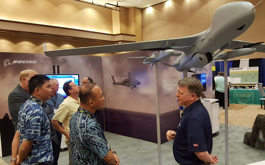 Visitors explore the exhibition hall at the Land Forces Pacific Symposium in Honolulu, Hawaii, Tuesday, May 21, 2019.