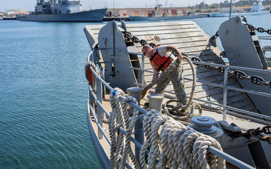 A 481st Transportation Company (Heavy Boats) soldier works the lines as the Landing Craft Utility 2000 disembarks from Port Hueneme, Calif., in 2015. The Army has suspended plans to shut down its watercraft units and auction off ships while while a congressional review is ongoing.