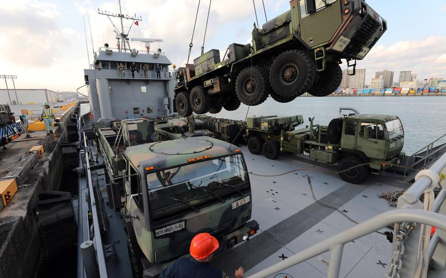 An M984A4 Heavy Expanded Mobility Tactical Truck is lowered onto a Landing Craft Utility (LCU) 2010 at Naha Military Port in Okinawa, Japan, in January 2019. The Army has suspended plans to shut down its watercraft units and auction off ships while while a congressional review is ongoing.