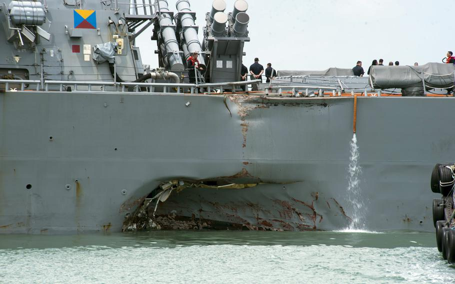 Damage to the left side is visible as the destroyer USS John S. McCain steers towards Changi Naval Base, Singapore, following a collision with a merchant vessel on Aug. 21, 2017. The Navy is replacing touch-screen throttles and helms on destroyers with hand-held ones after determining that the McCain's controls caused confusion that contributed to the collision.