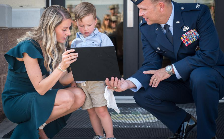 Alyssa Kidd and Beckham Kidd receive a replica of the plaque  that will go onto the newly named Kidd Weapons Load Training facility from Col. Michael Colvard, 2nd Maintenance Group commander at Barksdale Air Force Base, La., Aug. 16, 2019. Kidd was killed last fall in an attempted break-in of his vehicle outside his home in Bossier, La.