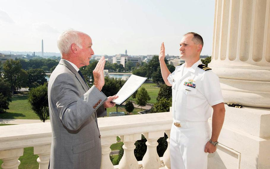 Jonathan Cebik takes the oath for promotion to lieutenant commander, administered by U.S. Rep. Joe Courtney, D-Conn., on Sept. 7, 2016.