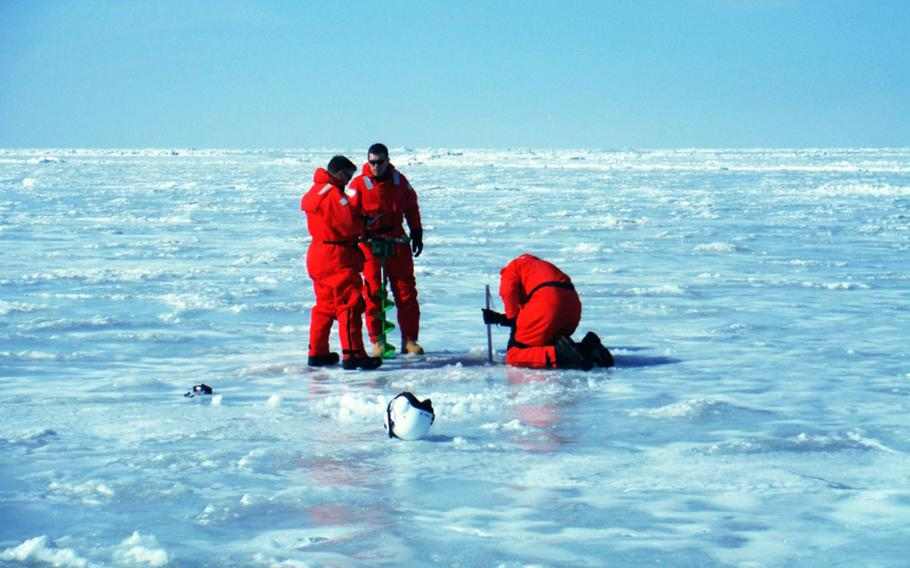 U.S. servicemembers measure ice thickness on Lake Erie with team members from Climate Change Canada, Feb. 22, 2019.